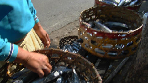 A man displays baskets of fresh fish on the side of a road Stock Video Footage