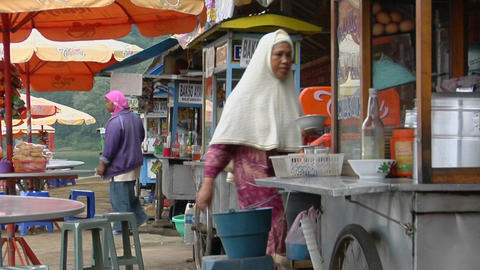 A woman wearing a Muslim dress carries a plate in an outdoor eatery Footage