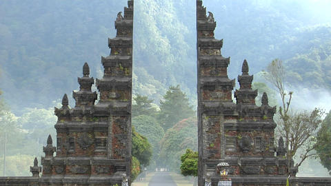 The fog drifts by a traditional Balinese temple gate in Bali, Indonesia Live Action