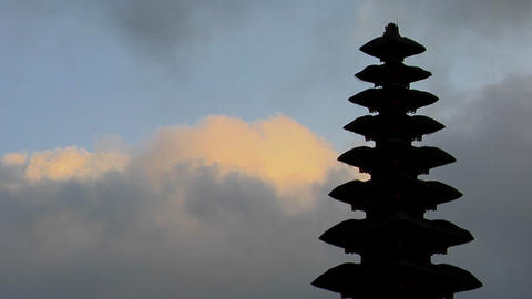 Part of a Balinese temple stands in silhouette Stock Video Footage