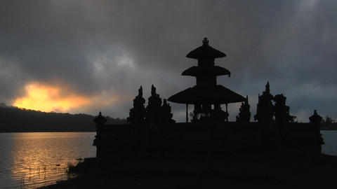 A Balinese temple overlooks reflections in a lake Live Action