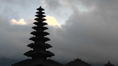 A Balinese temple stands silhouetted against a cloudy sky Stock Video Footage