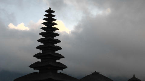 A Balinese temple stands silhouetted against a cloudy sky Footage
