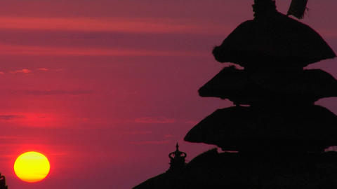 The Pura Tanah Lot Temple stands in silhouette against a glowing sky Footage