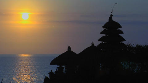 The sun silhouettes The Pura Tanah Lot temple during golden-hour Footage