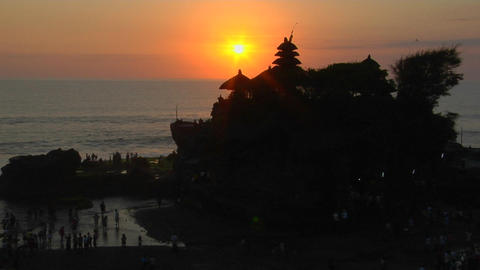 The sun silhouettes the Pura Tanah Lot temple in Bali, Indonesia Footage