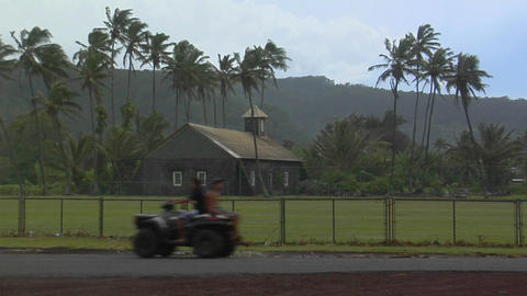 An ATV passes a distant church on a tropical island... Stock Video Footage