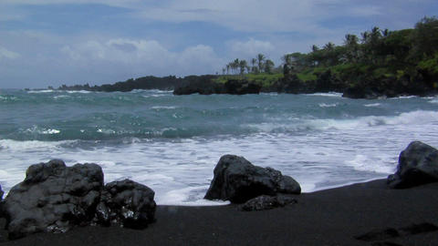 Large waves roll into a black sand beach Stock Video Footage