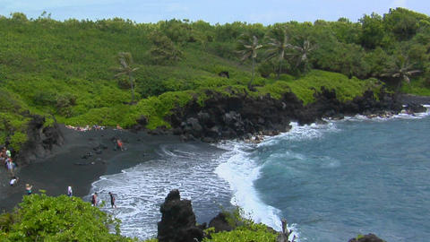 A high angle shot over waves rolling into a black sand... Stock Video Footage