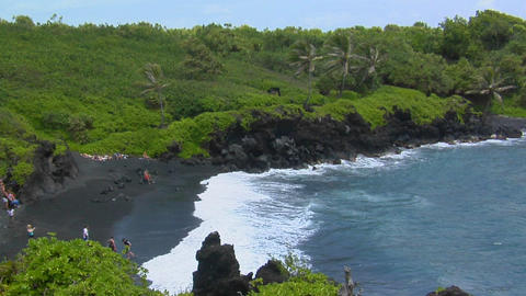 A high angle shot over waves rolling into a black sand beach in Hawaii Footage