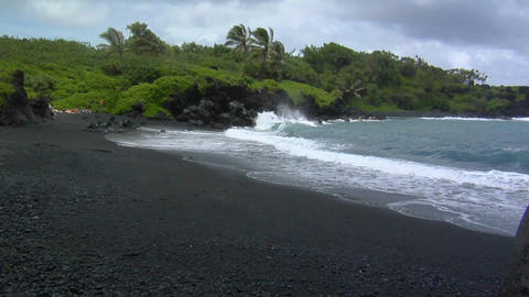 Waves roll into a black sand beach in Hawaii Stock Video Footage
