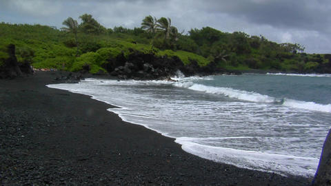 Waves roll into a black sand beach in Hawaii Footage