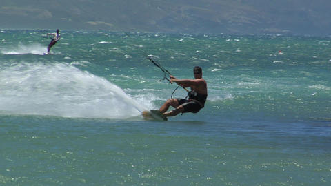 A windsurfer glides across a sparkling ocean Stock Video Footage