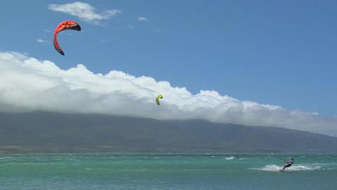 A wide shot of a windsurfer against a Hawaiian landscape Footage