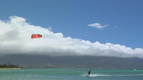 A wide shot of a windsurfer against a Hawaiian landscape Stock Video Footage