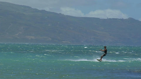 A windsurfer glides across the ocean and wipes out after... Stock Video Footage