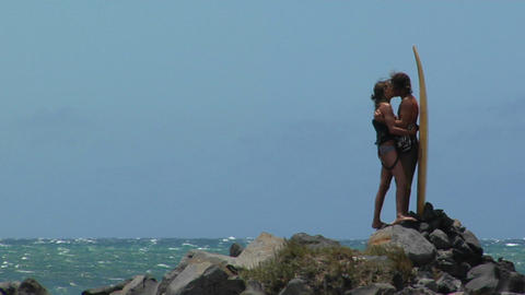 lovers kiss against an ocean background and a surfboard Stock Video Footage