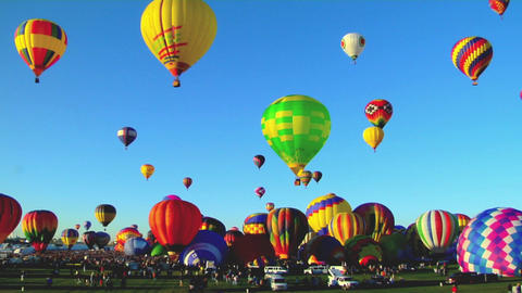 Hot air balloons rise against a blue sky at the... Stock Video Footage