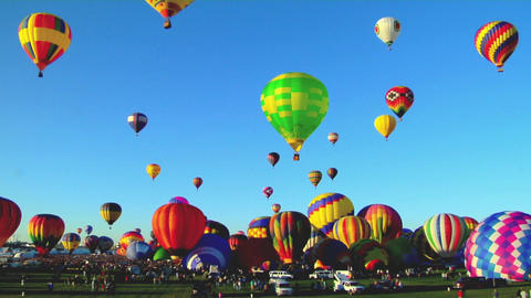 Hot air balloons rise against a blue sky at the Albuquerque Balloon Festival Footage