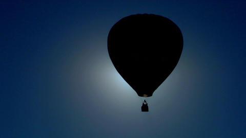 A hot air balloon crosses against the sun Footage
