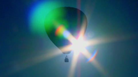 A hot air balloon crosses against the sun Stock Video Footage