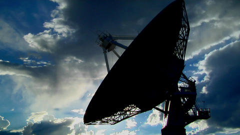 A satellite dish is moves and is silhouetted against the sky Stock Video Footage