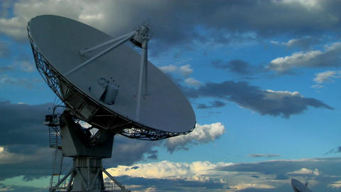 A satellite dish moves in time lapse against a beautiful sky Footage