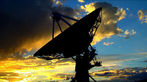 A satellite dish moves in time lapse against a beautiful sky Stock Video Footage