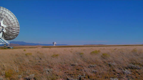 Pan across a windblown field to a satellite dish Stock Video Footage