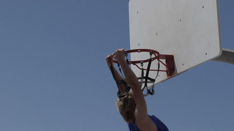A man dunks a basketball and hangs on the rim for awhile Stock Video Footage