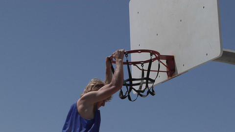 A man dunks a basketball and hangs on the rim for awhile Footage