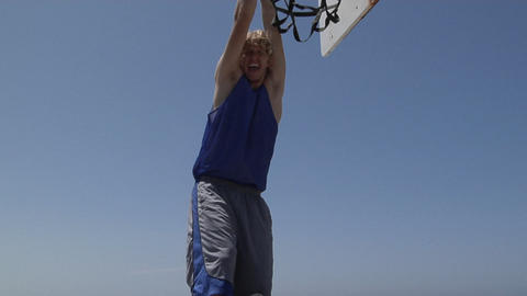 A basketball player slam dunks while standing on a step ladder Footage
