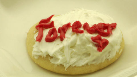"""A woman's hand picks up a cookie with the words Forever""""... Stock Video Footage"""