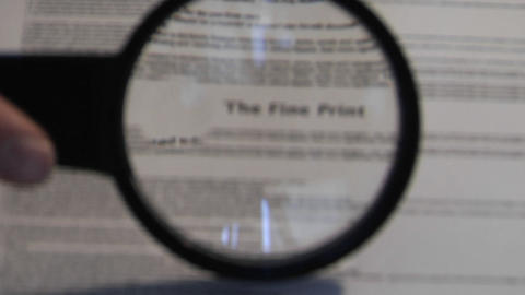A magnifying glass passes over a paper revealing the... Stock Video Footage