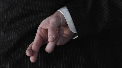 A businessman crosses his fingers behind his back Stock Video Footage