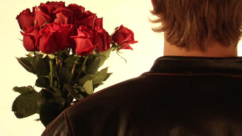 A man holds flowers in his hand and a cleaver behind his back Footage