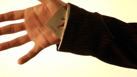A man tucks a playing card into his shirt sleeve Stock Video Footage