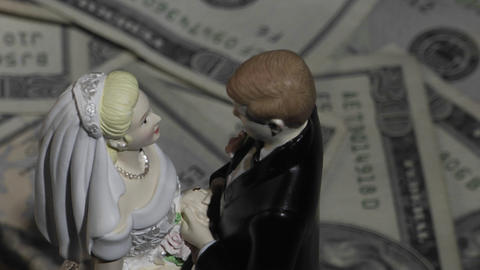 A married couple figurine stands amid twenty dollar bills Stock Video Footage