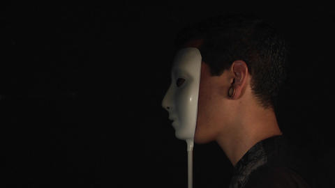 A man stands in profile then holds a white mask to his face Stock Video Footage