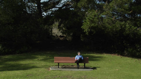 A man sits on a park bench alone with a flower Footage