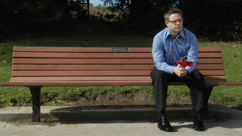 A man sits alone on a park bench with two flowers Footage