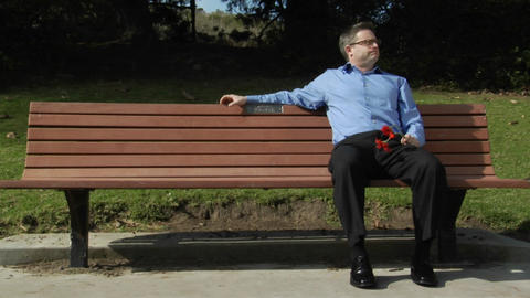 A man sits alone on a park bench with two flowers Stock Video Footage