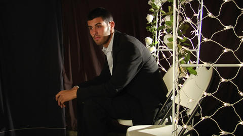 A groom sits in a folding chair under a flower arch Stock Video Footage