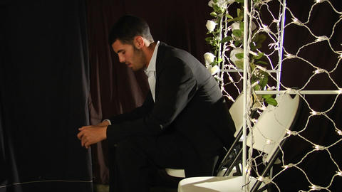 A groom sits in a folding chair under a flower arch Footage