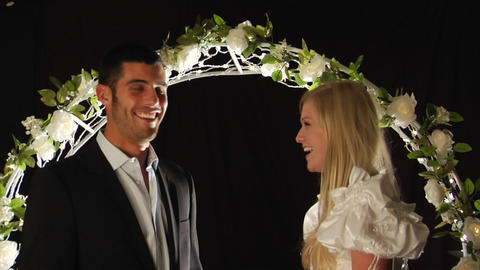 Bride and groom laughing under a flower arch Stock Video Footage