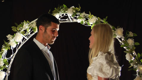Bride and groom laughing under a flower arch Footage