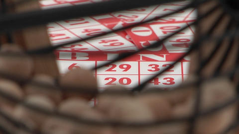 A cage of bingo balls spins in front of bingo cards Stock Video Footage