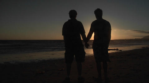 Silhouettes of two men hold hands on a windy beach Stock Video Footage
