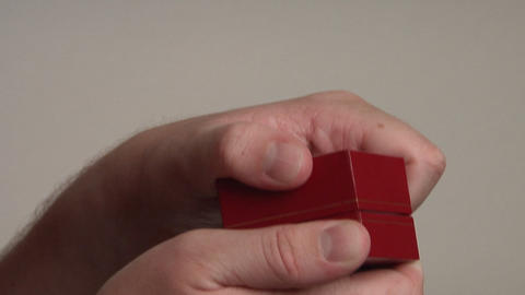 A man's hands open a red jewelry box that reveals a pearl... Stock Video Footage