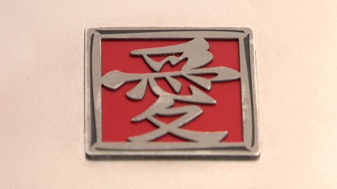 A red and silver square with Asian characters lies on a pink surface Footage